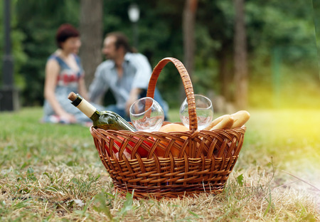 romantic couple on a picnic with a basket in the foreground