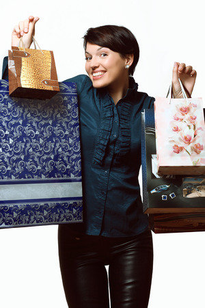 happy girl in a blouse and pants with packages in hands