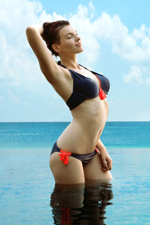 girl boobs: young and sexy girl in a blue bathing suit standing in blue water