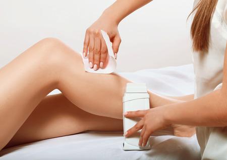 depilacion con cera: chica hace una depilación con cera en sus pies para el cliente, piel sedosa en las mujeres