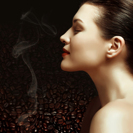 young girl models: beautiful girl inhales the aroma of the coffee beans Stock Photo