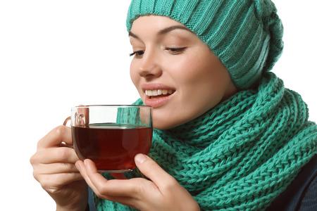 Pretty girl in scarf and hat drinks tea from a large cup