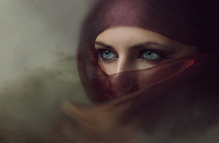 asian girl face: Young arabian woman in hijab with sexy blue eyes. Yashmak. Stock Photo