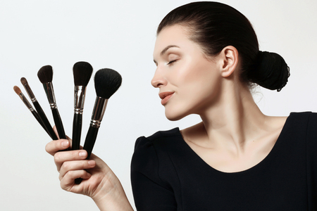 beautiful and young woman with brushes for make-up, makeup artist Фото со стока