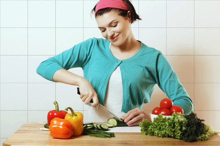 Beautiful and happy girl preparing a salad, a housewife, fresh vegetables, cooking Фото со стока