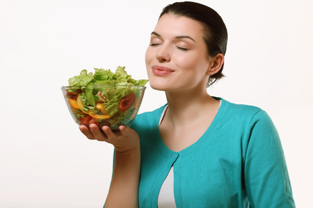 Beautiful and happy woman holding a delicious salad. Fresh vegetables, healthy diet.