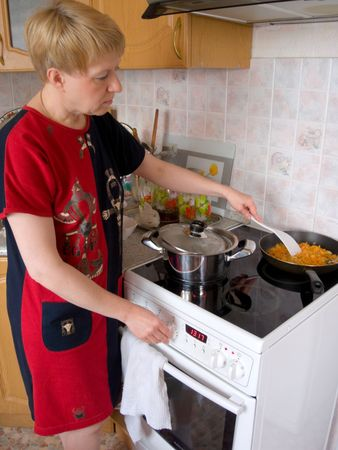efforts: House efforts. The woman cooks  food on a cooker.