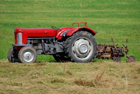 Old red tractor on field with hay photo