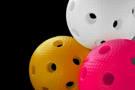 Three floorball balls isolated on a black background  white, orange  and pink