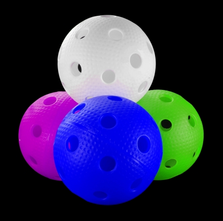 Four floorball balls isolated on a black background  white, purple, blue and lime