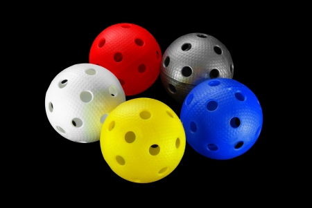 Five floorball balls isolated on a black background  white, yellow, blue, silver  and red   Standard-Bild