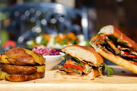 rukola: Royal Large Size Sandwich Cut in Half with Grilled Vegetables Rukola and Parmesan Cheese and Baked Potatoe on the Side atop a Light Color Wooden Board Stock Photo