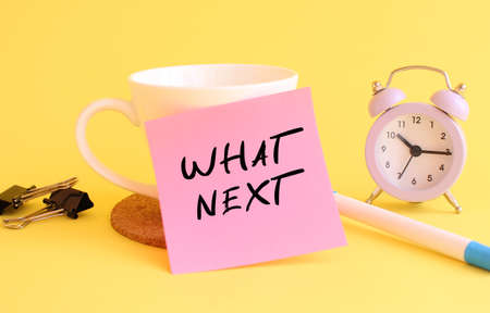 Pink paper with the text WHAT NEXT on a white cup. Clock, pen on a yellow background.