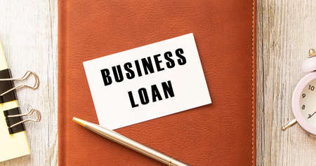 Text BUSINESS LOAN on white card lying on notepad on office desk.
