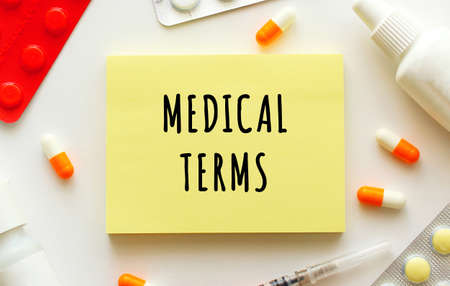 Notepad with text MEDICAL TERMS on a white background. Nearby are various medicines.