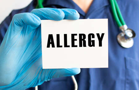 Doctor holding a card with text ALLERGY. Medical concept.