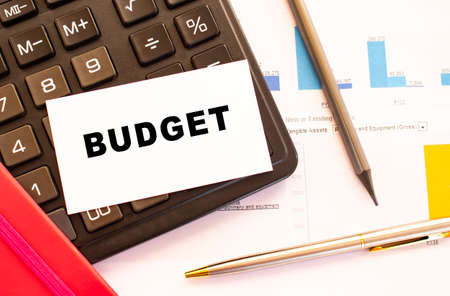 Text BUDGET on white card with metal pen, calculator and financial charts. Business and financial concept