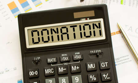 A calculator labeled DONATION lies on financial documents in the office.