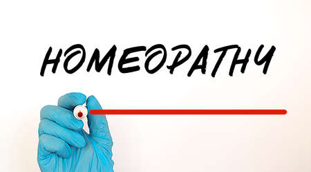Doctor writing text HOMEOPATHY with red marker.