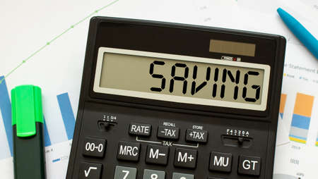 A calculator labeled SAVING lies on financial documents in the office. Business concept.