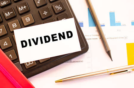 Text DIVIDEND on white card with metal pen, calculator and financial charts. Business and financial concept Stock Photo