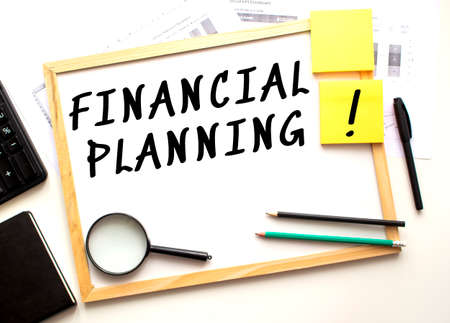 FINANCIAL PLANNING text is written on a white office board. Work table with office supplies. Business and financial concept.