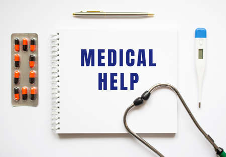 MEDICAL HELP is written in a notebook on a white table next to pills and a stethoscope. Medical concept