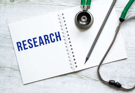 RESEARCH is written in a notebook on a light wooden table next to pencil and a stethoscope. Medical concept