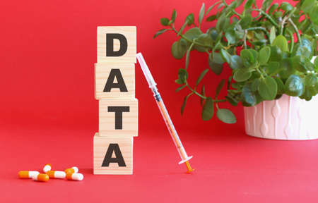 The word DATA is made of wooden cubes on a red background with medical drugs.