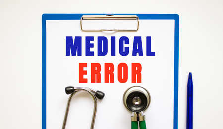 Clipboard with page and text MEDICAL ERROR, on a table with a stethoscope and pen. medical concept.