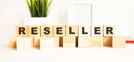 Wooden cubes with letters on a white table. The word is RESELLER. White background with photo frame, house plant. Stock fotó