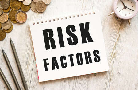 RISK FACTORS text on a sheet of notepad. Coins are scattered, pencils on a gray wooden background. Financial concept. Stock fotó