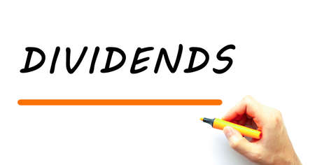 Hand writing DIVIDENDS with marker. Isolated on white background. Business concept.