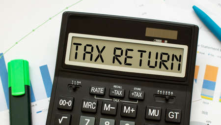 A calculator labeled TAX RETURN lies on financial documents in the office. Business concept.