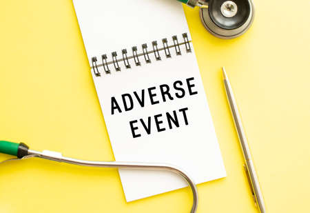 ADVERSE EVENT is written in a notebook on a color table next to pen and a stethoscope. Medical concept Stock fotó