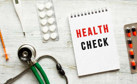HEALTH CHECK is written in a notebook on a white table next to pills and a stethoscope. Medical concept