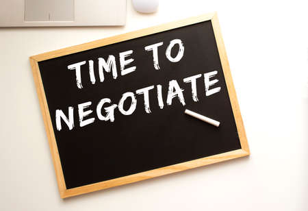 Text TIME TO NEGOTIATE written in chalk on a slate board. Office desk. Business concept. Stock fotó