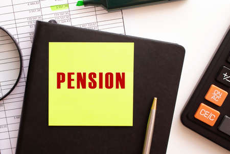 PENSION text on a sticker on your desktop. Diary, calculator and pen. Financial concept.