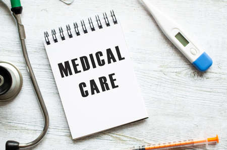 MEDICAL CARE is written in a notebook on a light wooden table next to a stethoscope. Medical concept