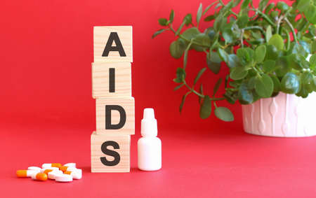 The word AIDS is made of wooden cubes on a red background with medical drugs.
