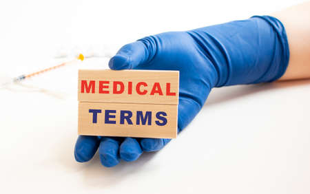 A hand in a medical glove holds wooden cubes with the inscription MEDICAL TERMS. Medical concept.