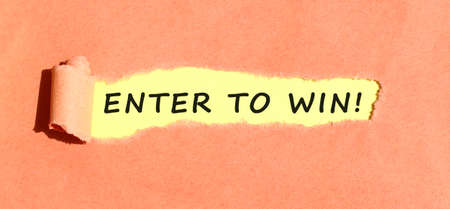 The text ENTER TO WIN appearing on yellow paper behind torn color paper. Stock fotó