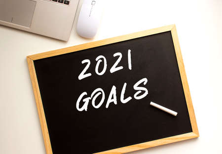 Text 2021 GOALS written in chalk on a slate board. Office desk. Business concept.