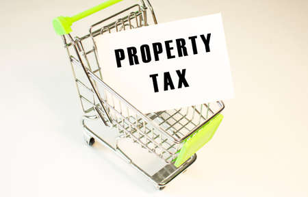 Shopping cart and text PROPERTY TAX on white paper. Shopping list concept on light background.