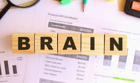 Wooden cubes with letters on the table in the office. Text BRAIN. Financial concept.