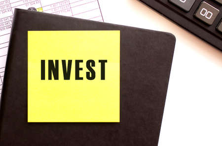 INVEST text on a sticker on your desktop. Diary and calculator. Financial concept.