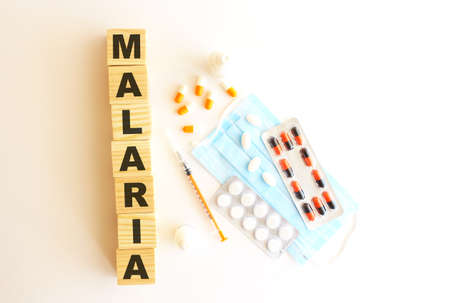 The word MALARIA is made of wooden cubes on a white background with medical drugs and medical mask.