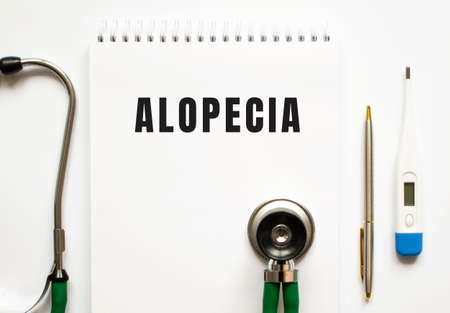 ALOPECIA text written in a notebook lying on a desk and a stethoscope. Medical concept.