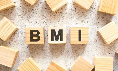 The word BMI consists of wooden cubes with letters, top view on a light background. Work space.