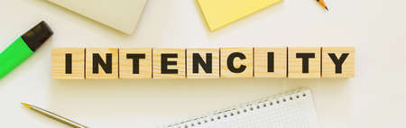 Wooden cubes with word INTENCITY on the office desk. Folder and other office supplies. Work space. Stock Photo
